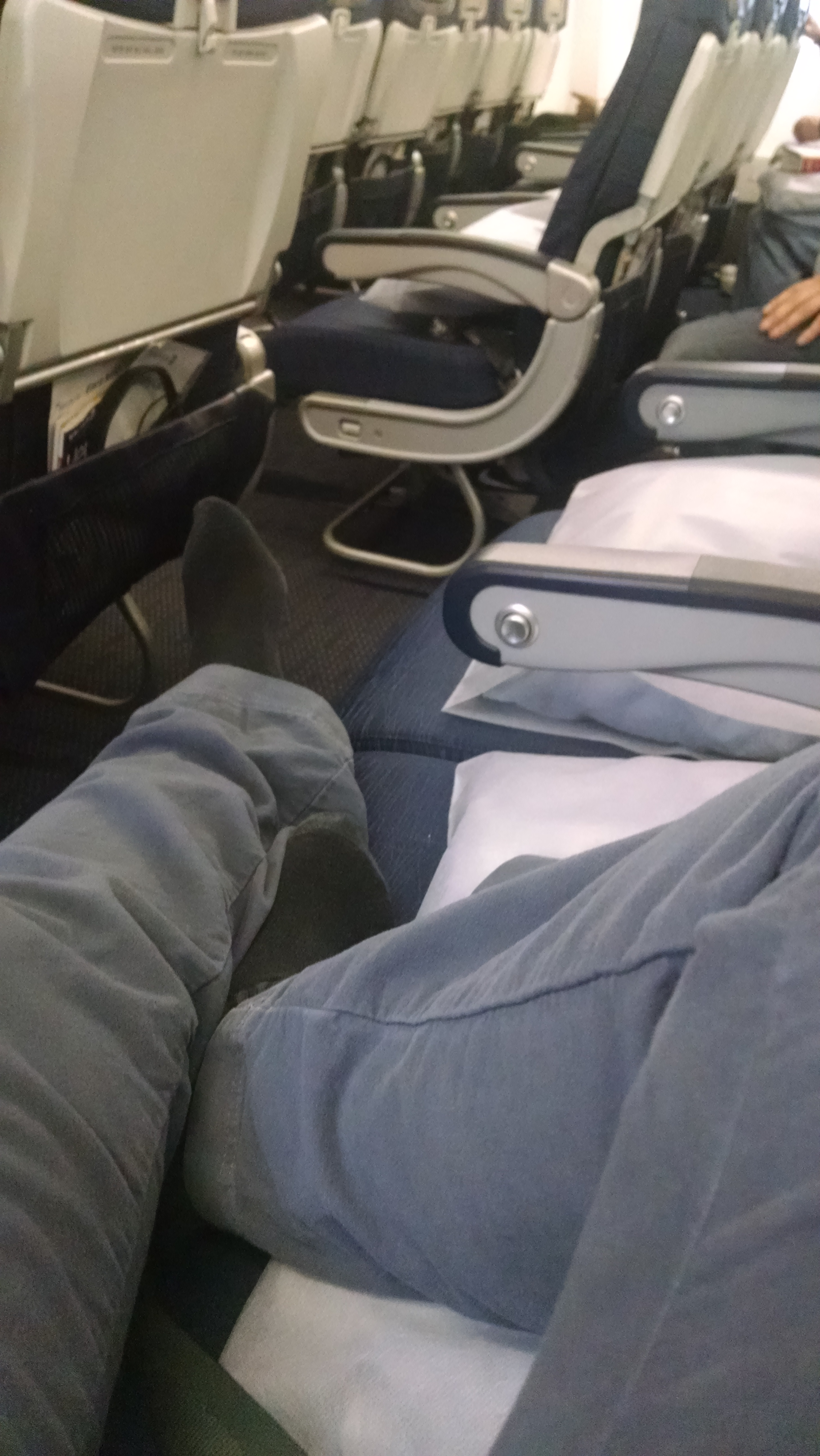 Legs across empty airplane seats