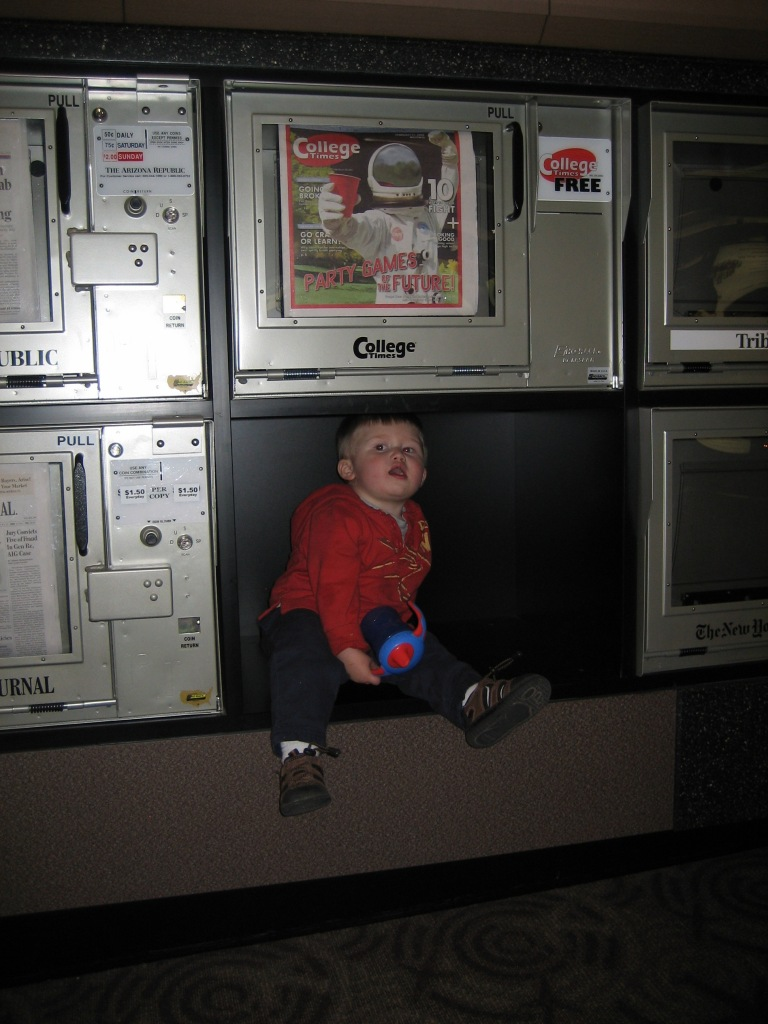 small child in a newspaper dispenser